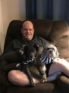 bald man on couch holding black dog and light brown dog